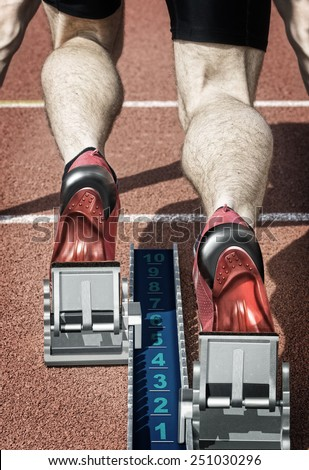 Top view of a male short track runner in the blocks. Desaturated hard colors and with own design replaced running shoes and start block are underlining the illustration effect of the photo. - stock photo