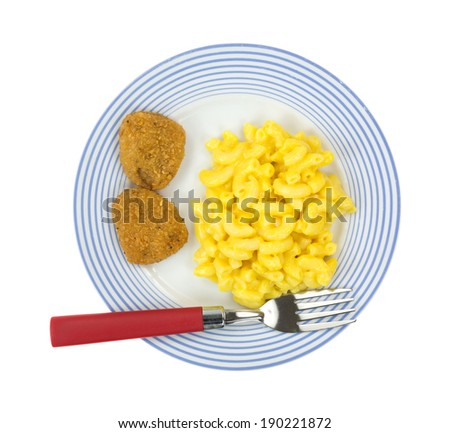 Top view of a meal of macaroni and cheese with two chicken nuggets on a blue striped plate with a red handled fork. - stock photo
