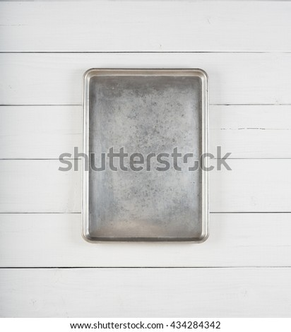 Top View of a Metal Cookie Sheet Cooking Pan Laying or Hung Vertical centered on a Rustic White Gray Wood Board Background with room or space for copy, text, your words or ideas.Planks are horizontal