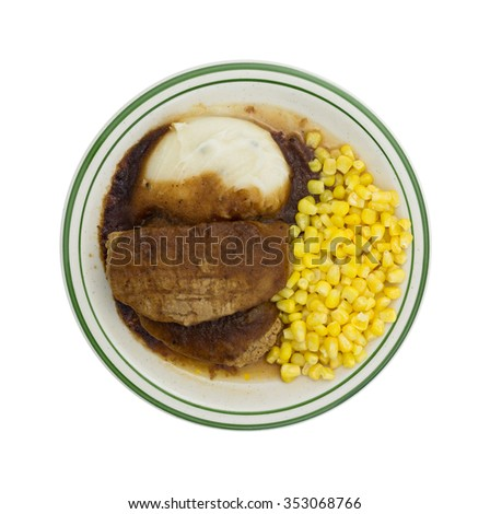 Top view of a microwaved meatloaf with gravy plus mashed potatoes and corn TV dinner on a plate isolated on a white background. - stock photo
