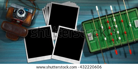 Top view of a mini foosball with an old and vintage camera and a group of empty instant photo frames. On a wooden blue desk - stock photo