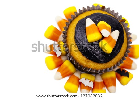 Top view of a muffin decorated with candy corn and chocolate cream over white background. - stock photo