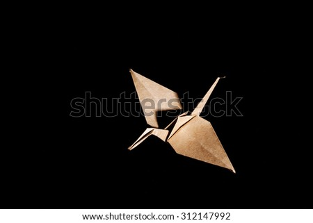 Top view of a origami crane (bird) made from brown recycle paper isolated on black background - stock photo