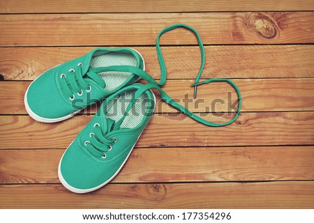 Top view of a pair of shoes with laces making heart shape on wooden floor. Heart made of shoelaces - stock photo