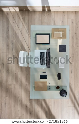 top view of a perfectly tidy glass desk with a laptop and a smart phone and other objects in the same color tone, sun casts graphics shadows  on the wooden floor - stock photo