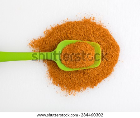 Top view of a portion of Cajun seasonings on a green spoon atop other seasonings on a white cutting board. - stock photo