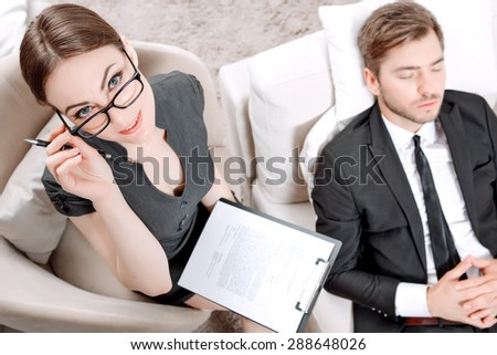 Top view of a psychologist sitting in the armchair holding a clipboard in her hands and looking at us while her client lying on a couch near relaxing ,thinking of his problems during therapy session - stock photo