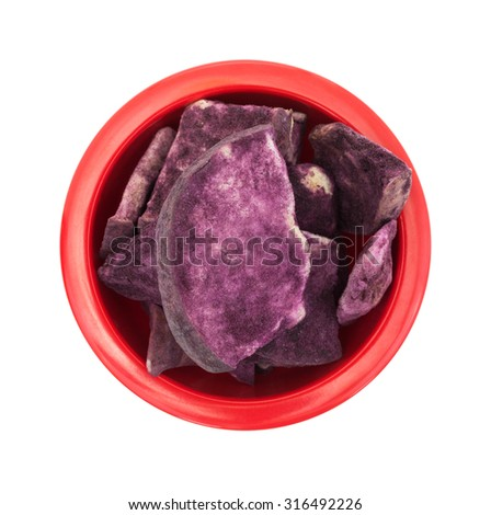 Top view of a red bowl filled with freeze dried apple slices coated with Maqui berry powder isolated on a white background. - stock photo