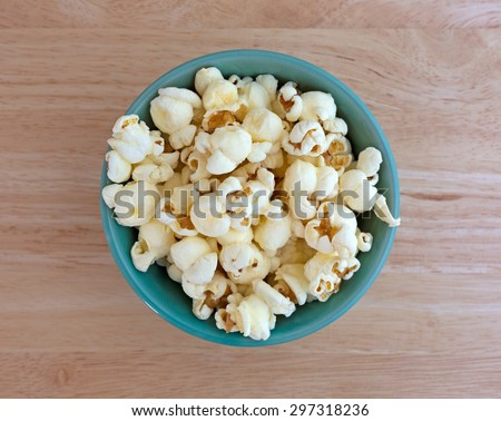 Top view of a small bowl filled with a serving of white cheddar cheese flavored popcorn on a wood table top illuminated with natural light. - stock photo