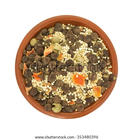 Top view of a small bowl filled with the dry ingredients for quinoa lentil soup isolated on a white background. - stock photo