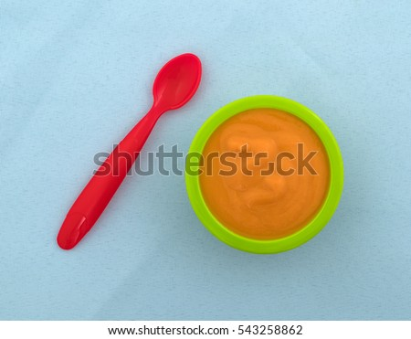 Top view of a spoon with a serving of banana carrot and mango baby food in a green bowl atop a wrinkled blue tablecloth.