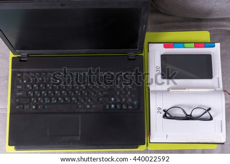 Top view of a tabletop workstation with open laptop, a diary, glasses and mobile phone are arranged in strict order on it - stock photo