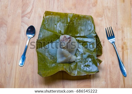 Top view of a traditional food in Vietnam call Banh Gio or pyramid shaped. Make from rice flour dumpling filled with pork , shallot and mushrooms , wrapped in banana leaf. Delicious street food.