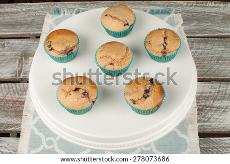 top view of a white cake stand with fresh homemade blueberry whole wheat muffins on an old barn wood table - stock photo