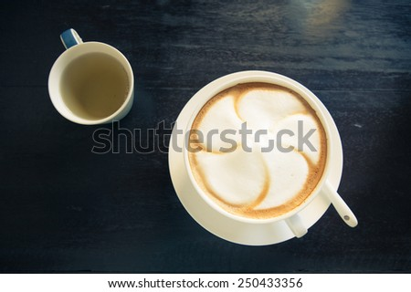 Top view of a white cup of hot cappuccino coffee with tea on white saucer, isolate over grunge wood - stock photo