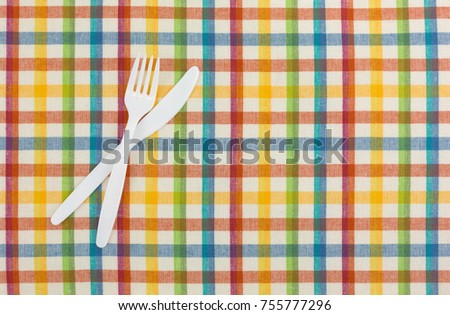 Top view of a white plastic fork and knife on a colorful tablecloth.