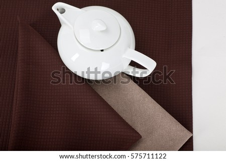 top view of a white teapot on a brown tablecloth