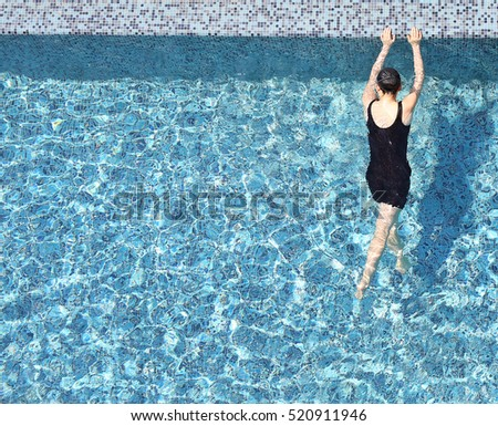 Top view of a woman in the swimming pool with copy space.