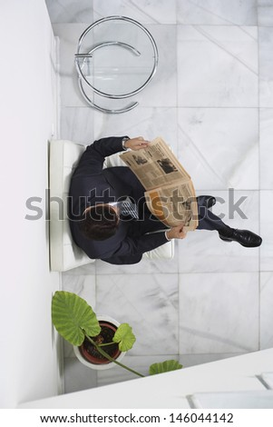 Top view of a young businessman reading newspaper in the office lobby - stock photo