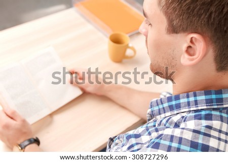 Top view of a young student sitting at the table holding a book and reading it preparing for exams at university, selective focus