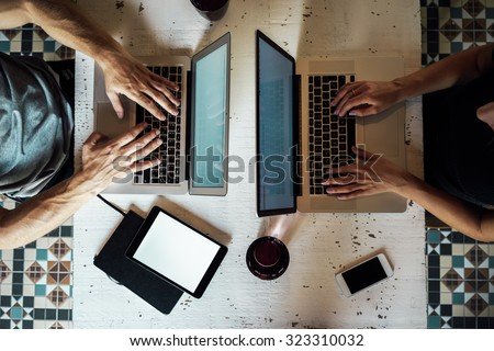 top view of a young woman and a young man who works with a laptops. phone and tablet on the table.  digital tablet with blank copy space screen for your information - stock photo