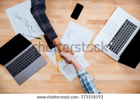 Top view of african and caucasian men shaking hands after working with reports on laptops - stock photo