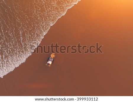 Top view of air shooting from flying drone of a young businesswoman is using net-book for distance work,while is lying on a longer on a beach with copy space during her summer travel in Thailand - stock photo