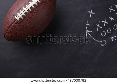 Top view of an American style football on a chalkboard with a play diagramed. Horizontal format with copy space.