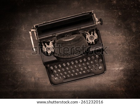 Top view of an old typewriter on a wooden table - warm effect - stock photo