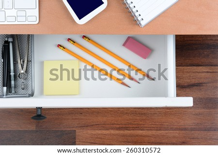 Top view of an open desk drawer showing the items inside. The top of the desk has a computer keyboard Cell Phone and note pad. The neat drawer has pencils paper and organizer. - stock photo