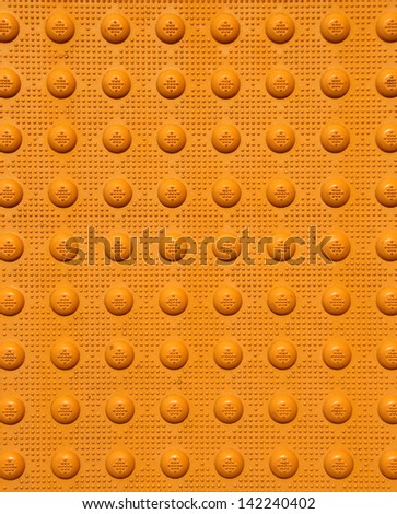 Top view of an orange sidewalk warning pad. - stock photo