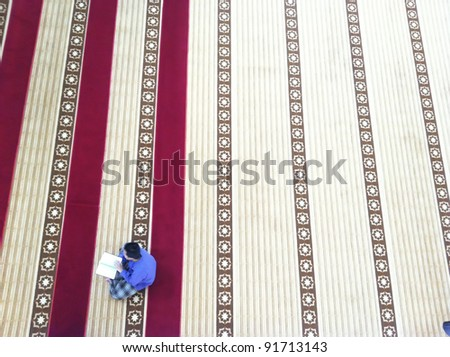 Top view of an unidentified male Muslim read Quran (koran) in a masjid (mosque). - stock photo
