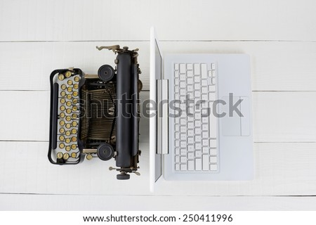 Top view of and old fashioned typewriter back-to-back with a modern laptop computer on w white wood desk.  - stock photo