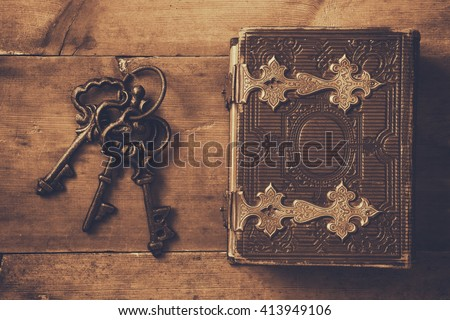 top view of antique book cover, with brass clasps and old keys. sepia vintage filtered. selective focus