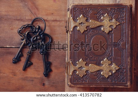 top view of antique book cover, with brass clasps and old keys. vintage filtered. selective focus  - stock photo