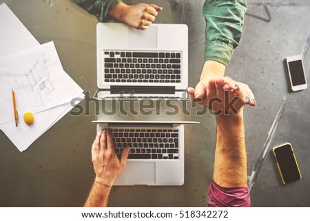 Top view of architects giving high-five while working at computer in office