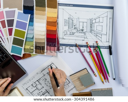 Top view of architects hands drawing of modern house with material sample on creative desk - stock photo