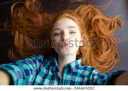 Top view of attractive playful young woman with beautiful red hair in checkered shirt making selfie and sending air kiss lying on the floor - stock photo