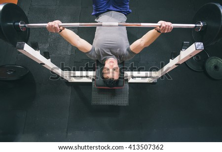 Top view of attractive young muscular man lifting weight while working out in gym - stock photo
