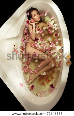 Top view of beautiful woman relaxing in bath with rose petal and candles. Body care. - stock photo