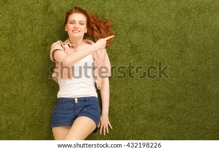 Top view of beautiful woman with red hair lying on green grass and showing something with her point finger in park line. - stock photo