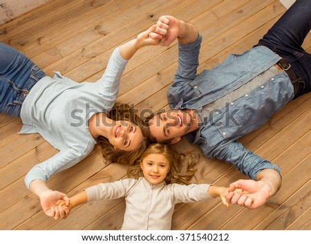 Top view of beautiful young family looking in camera, smiling and holding hands while lying on wooden floor at home - stock photo