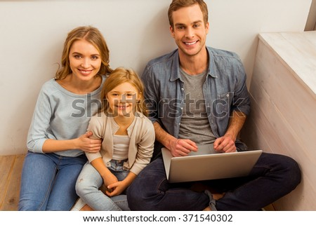 Top view of beautiful young family using laptop and smiling while sitting on the floor near the window at home - stock photo
