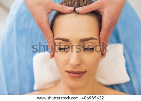 Top view of beautiful young woman getting a face massage, lying with closed eyes - stock photo
