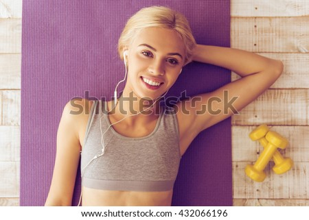 Top view of beautiful young woman in headphones listening to music, looking at camera and smiling while lying on yoga mat - stock photo