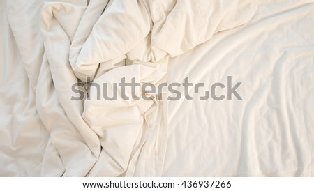 Top view of bedding sheets and blanket texture abstract background with sunlight in the morning : vintage tone