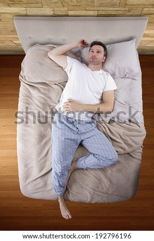 top view of bedroom with insomniac man unable to sleep - stock photo