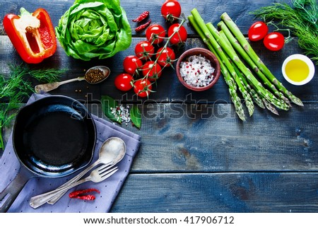 Top view of bio healthy food, herbs and spices on rustic wooden background. Colorful vegetables ingredients for tasty vegan and diet cooking. Vegetarian food concept. - stock photo