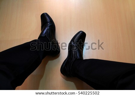 Top view of black pants and leather shoes of relax sitting businessman on wood floor  Photo is focused at shoes