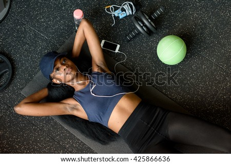 Top view of black sexy fit woman doing press ups in the gym and listening to music in earphones - stock photo